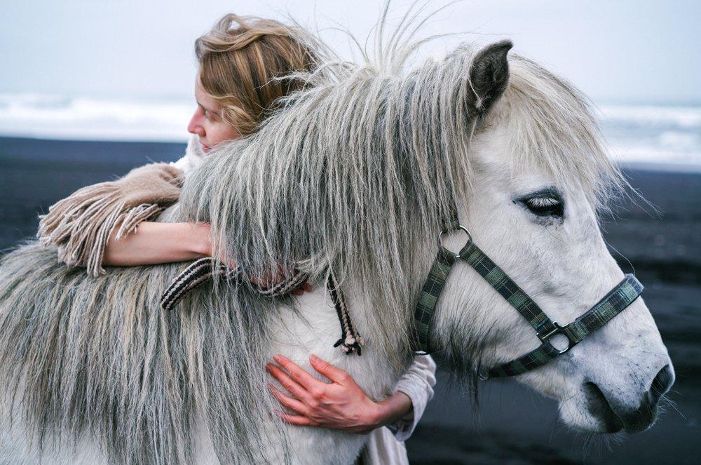Eine Frau kuschelt mit einem Pony mit dickem Winterfell.